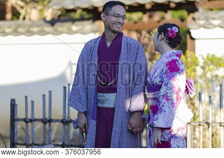 Kyoto, Japan - November, 8, 2019: Young Lovely Couple In Geisha Silk Kimono Posing On One Of The Kyo