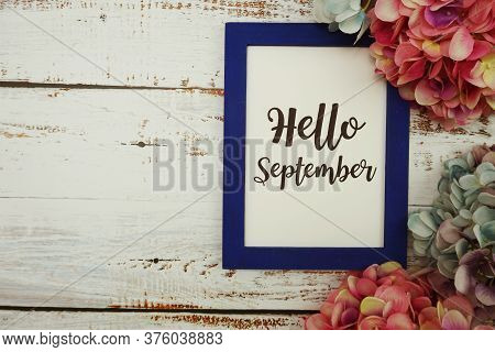 Hello September Card With Colorful Flowers Border Frame On Wooden Background