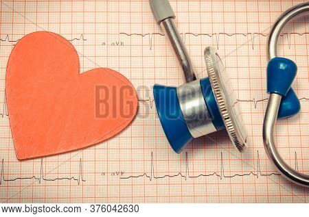 Medical Stethoscope And Red Heart Shape Lying On Electrocardiogram Graph Report. Ekg Heart Rhythm. M