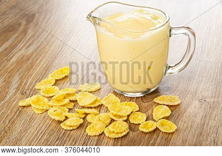 Scattered Cornflakes, Pitcher With Fruit Yogurt On Brown Wooden Table