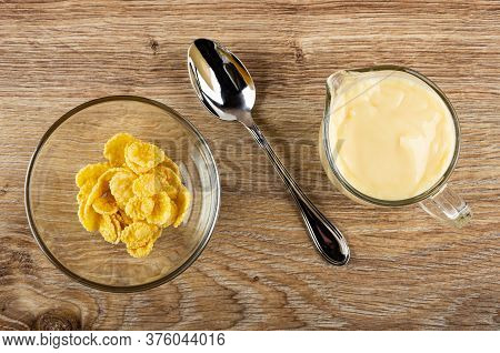 Transparent Glass Bowl With Corn Flakes, Spoon, Pitcher With Fruit Yogurt On Brown Wooden Table. Top