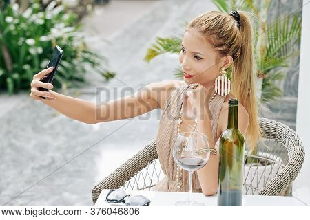 Atractive Young Vietnamese Woman Sitting At Outdoor Cafe With Glass Of Wine And Taking Selfie