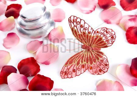 Pile Of Round Pebble Stones With Butterfly And Rose Petals
