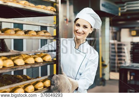 Baker woman pushing sheets with bread in the baking oven wearing bakers mittens