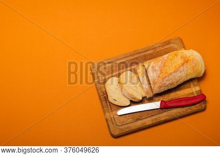 Sliced Bread Baguette On A Wooden Cutting Board With Knife On A Terracote Color Background. Copy Spa