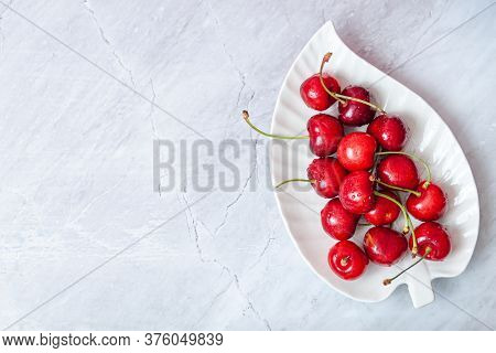 Cherry On Decor Plate On Grey Background. Ripe Ripe Cherries. Sweet Red Cherries. Top View. Rustic S
