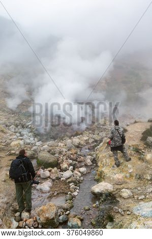 Group Of Tourists And Photographer Walking Through Volcanic Landscape: Eruption Fumarole, Hot Spring