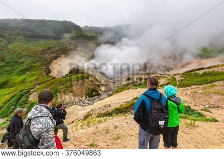 Group Of Tourists And Travelers Watching Beautiful Volcanic Landscape, Eruption Fumarole, Hot Spring