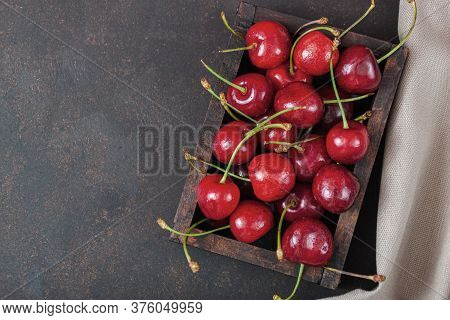Cherry With Leaf Water Drops On Wooden Box On Dark Brown Stone Table. Ripe Ripe Cherries. Sweet Red