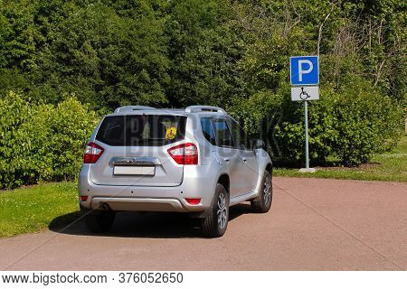 Silvery Car With Badge Disabled In The Parking Lot With Road Sign Parking For Disabled Drivers. Push