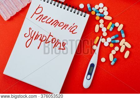 Notepad, A Variety Of Medicines, Thermometer, Syringe And Ampoules With Medicine On A Red Background