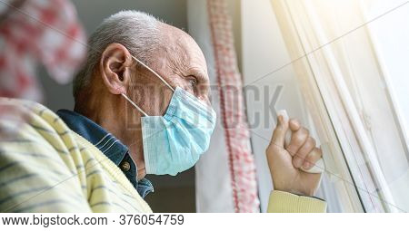 Pensioner In Face Mask And Yellow Pullover Holds Hand On Window Handle Standing Under Summer Sunligh