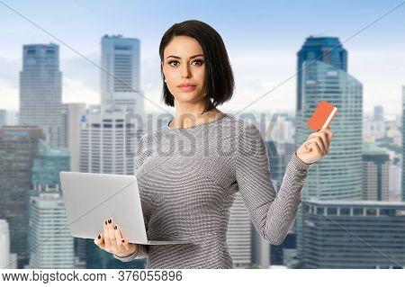 Portrait Of Confident Businesswoman Hold Laptop And Bank Card In Her Hands Over City Background