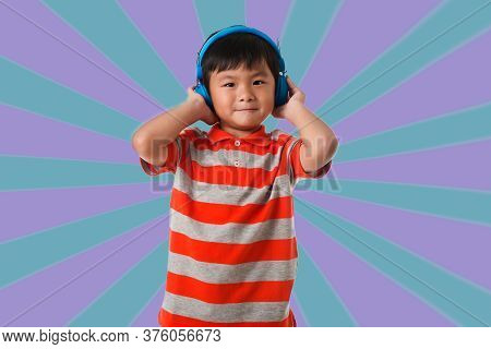 Music And Technology Concept.asian Little Boy With Headphone Over Geometric Background