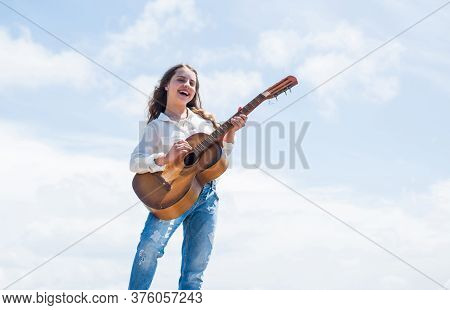 Little Girl Play Guitar She Loves Music. Music School Classes. Small Guitar Player On Sky Background