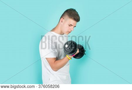 Teen Boy Training With Barbells. Sport And Fitness. Teen Guy Hold Dumbbell. Sportswear And Equipment