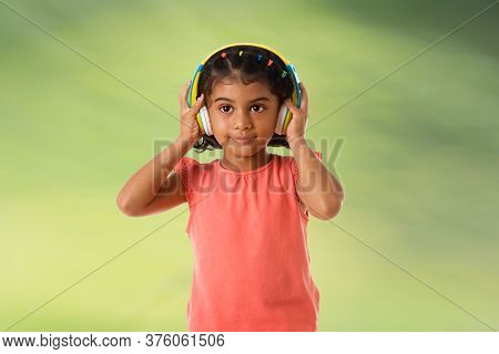 Music,childhood And Technology Concept.child With Headphones On Green Background