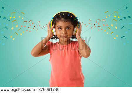 Music, Childhood And Technology Concept- Little Indian Girl With Headphones Over Green Color Backgro