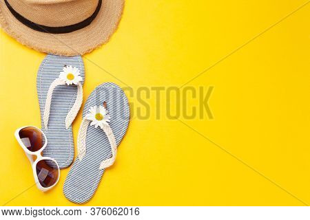 Summer vacation items and accessories. Flip flops, sunglasses and sun hat on yellow background. Top view flat lay with copy space