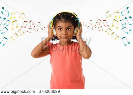 Music, Childhood And Technology Concept- Little Indian Girl With Headphones Over White Backgroundoun