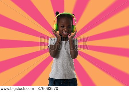 Music, Childhood And Technology Concept.lovely Happy Little Girl With Headphones Over Geometric Back