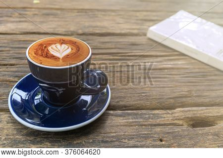 Close Up Of Hot Cappuccino Coffee In The Cafe, Heart Shaped Cappuccino Coffee In Blue Cup On A Woode