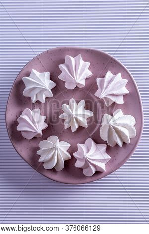 Close-up Of Few Delicate Pink Meringue Cookies On Pink Porcelain Round Plate. Textured White Paper B
