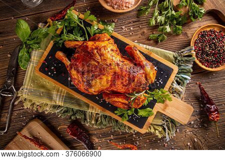 Flat Lay Of Oven Baked Whole Chicken On Slate Cutting Board