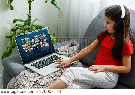 Girl In Headphones Sitting On Couch And Enjoying Interesting Movie. Watch Drama, Comedies, Documenta