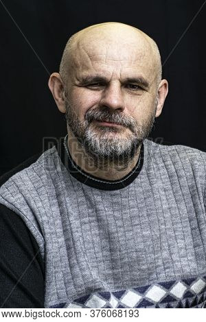 Middle-aged Bald Bearded Man Grins Contemptuously Against The Dark Background