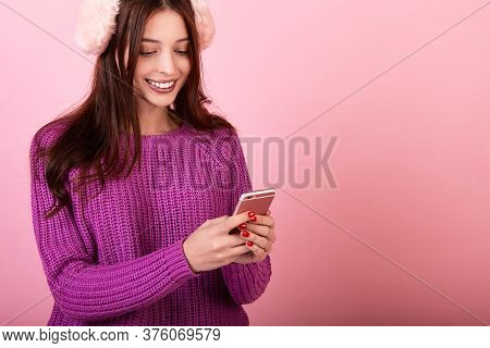 Sweet Girl In A Knitted Sweater And Fluffy Pink Headphones Holding A Phone. Looks And Smiles At The