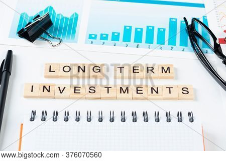 Long Term Investments Concept With Letters On Wooden Cubes. Still Life Of Office Workplace With Supp