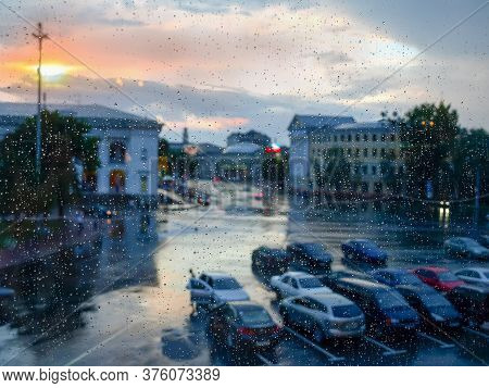 Window Pane During A Rain, Blurred Cityscape Through The Wet Glass Covered With Water Drops At Sunse