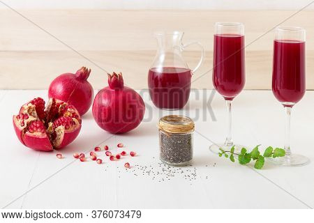 Pomegranates And Chia Seeds With Fresh Mint. A Glass Pitcher Of Fresh Red Juice With Two Full Tumble