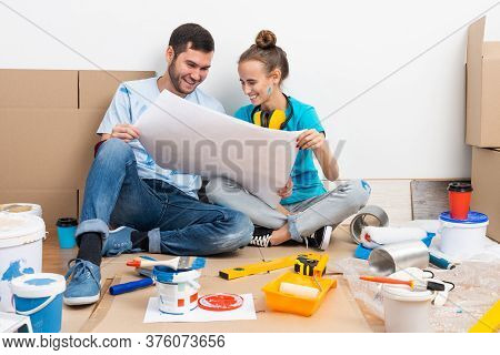 Happy Couple Sitting On Floor With Construction Blueprint. Home Remodeling And House Interior Redesi