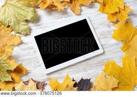 Tablet Computer With Blank Screen Lies On Vintage Wooden Desk With Bright Foliage. Flat Lay Composit