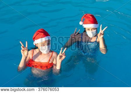 Two Little Girls In Santa Claus Hat And Medical Mask Swim In The Pool. New Year 2021 During The Pand