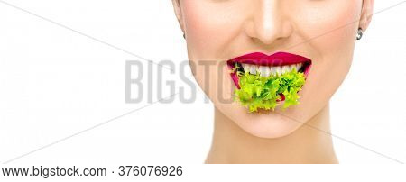Healthy eating, diet concept. Beautiful healthy girl eating raw vegan food and smiling. Lips. Beauty young fashion woman eats green fresh lettuce salad leaf, organic vegetables. Vegetarian. Makeup