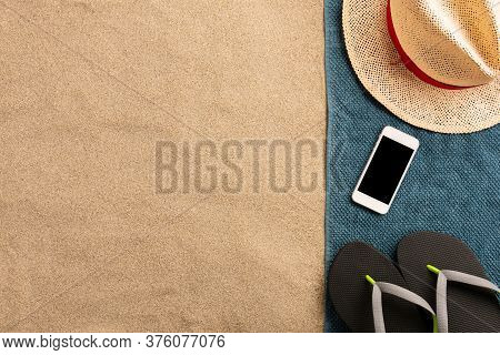 Summer Vacation Composition. Hat, Smartphone And Flip Flops On Sand. Harsh Light With Shadows. Summe