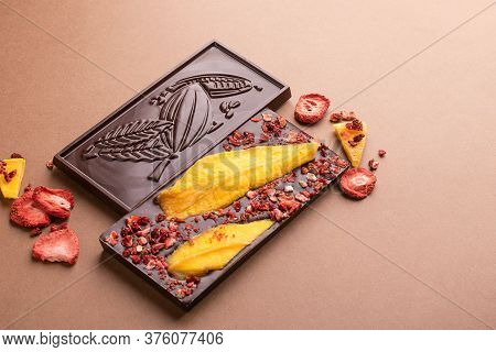 Chocolate Dark Belgian Bar With The Addition Of Fruit Slices Of Strawberry Mango On A Brown Backgrou