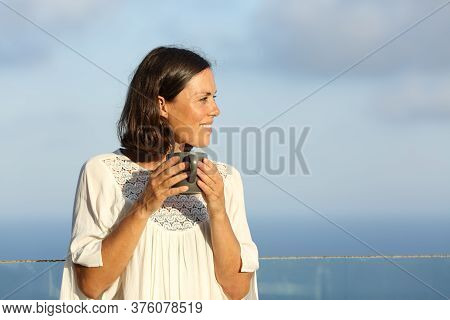Satisfied Adult Woman With Coffee Cup Looking Away Contemplating The Beach On A Balcony At Summer