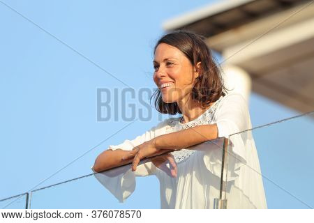 Happy Adult Woman Contemplates Looking Away On A Hotel Balcony On Vacation At Summer At Sunset