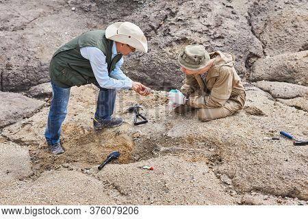Two Archaeologists Or Paleontologists In A Field Expedition Discuss The Ancient Bones Excavated By T