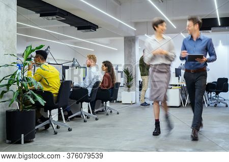 Group of businesspeople working in creative office. Interior of busy employees in a co-working space. Corporate businessmen and businesswomen sitting at desks and walking at work.