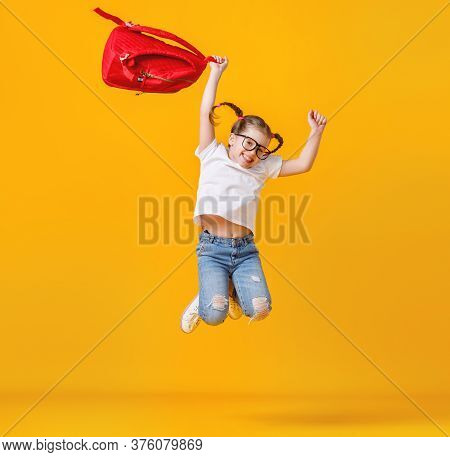 Full Body Excited Girl With Red Backpack Smiling And Leaping Up During Studies At School Against Yel