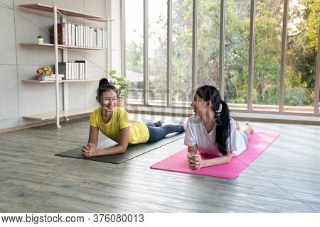 Two Happy Asian Women In Yoga Poses In Yoga Studio With Natural Light Setting Scene / Exercise Conce