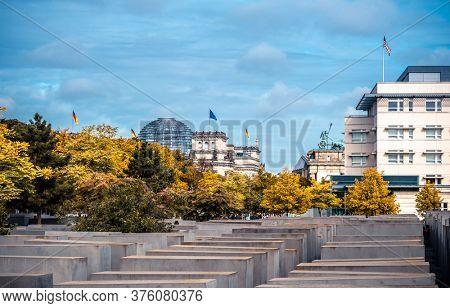 Berlin, Germany - 20 September 2019: Holocaust Memorial on german Reichstag background