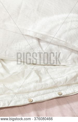 Trendy Organic Natural Linen Bedclothes With Wooden Buttons Closeup. Bedding, Morning Light, Bedroom
