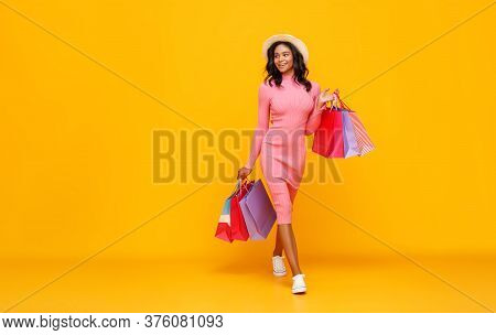 Cheerful Ethnic Woman With Paper Bags Smiling And Looking Away Over Shoulder While Walking Against Y