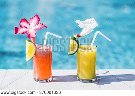 Two Glasses Of Fresh Cold Fruit Juice On Poolside. With Straw, Slice Of Lime And Tropical Flower